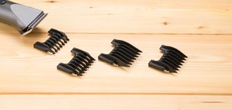 Electric hair clipper and 3 black nozzles, on a light wooden background. royalty free stock photos