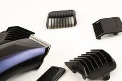 Electric hair clipper with different size attachments on a white background.  stock photo