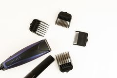 Electric hair clipper with different size attachments on a white background, top view.  stock photos