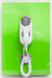 An electric hair dryer. Attached to a wall on a green background royalty free stock photo