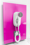 An electric hair dryer. Attached to a wall on a pink background royalty free stock images