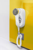 An electric hair dryer. Attached to a wall on a yellow background stock photography