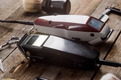 Electric hair trimmers macro. Electric hair trimmers, close-up. Brush, scissors and a straight razor on the wooden surface. Haircuts for men stock image