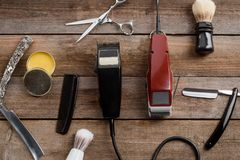 Electric hair trimmers and wax. Electric hair trimmers, a comb, a brush, straight razors, scissors, wax on the wooden surface, a top-view image. Barber tools stock photos
