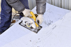 Electric hand tool in the hands of the worker, cutting sheet met Stock Photography