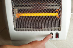 Electric heater and hand which includes switch Stock Photo