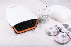 Electric heater, pair of warm slippers and Christmas lantern on white furry carpet. Winter background Stock Photography