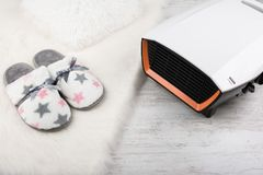 Electric heater and pair of warm slippers on white furry carpet. Winter background Royalty Free Stock Photos