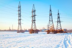 Electric high-voltage poles. In a snowy field Stock Photography