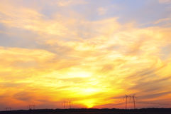 Electric high voltage poles stretching into the distance on the background of beautiful sunset sky Royalty Free Stock Photo