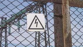 Electric high-voltage substation beyond the fence. Hazard warning sign. Danger to life. Energy industry. Electric wires. On the support. Risk of electric shock stock video