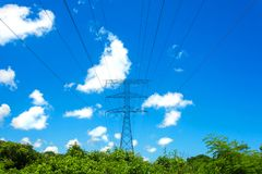 Electric tower. Electric high voltage tower on blue sky with white clouds background royalty free stock photo