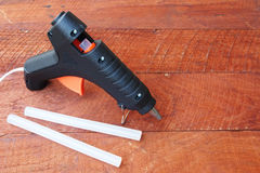 Electric hot glue gun on a wood background Stock Image