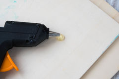 Electric hot glue gun on a wood background. the concept of repair or creativity background Stock Images