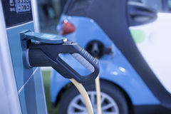 Electric hybrid car charging station with moving car Stock Photos