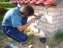Electric installation. Electrician, setting up new power cable socket Royalty Free Stock Photos