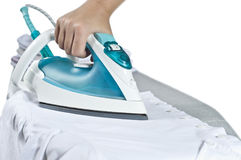 Electric iron. An electric iron on board and white shirt stock photo