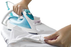 Electric iron. An electric iron on board and white shirt stock image