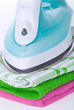 Electric iron and clothes Stock Photography