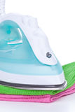 Electric iron and clothes Stock Photos