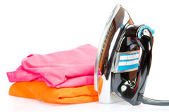 Electric iron and colorful clothes isolated on white Stock Photo