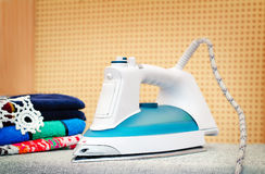Electric iron on the Ironing Board. Royalty Free Stock Images