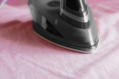 Electric iron on a mans pink shirt Stock Images