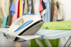 Electric iron and shirt. On cloth background Stock Photo