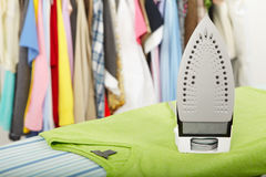 Electric iron and shirt. On cloth background Royalty Free Stock Image