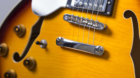 Electric jazz guitar close up on an orange sunburst color and chrome electronics Stock Image