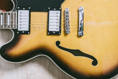 Electric jazz guitar close up on an orange sunburst color and chrome electronics Royalty Free Stock Photos