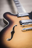 Electric jazz guitar close up on an orange sunburst color and chrome electronics Stock Photos