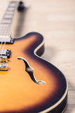 Electric jazz guitar close up on an orange sunburst color and chrome electronics Royalty Free Stock Image