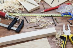 Electric jigsaw with many wooden bricks full of sawdust. On old scratched wooden table, work tools concept Stock Image