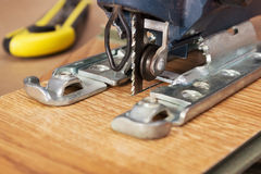 Electric jigsaw sawed easily laminated panel Royalty Free Stock Photography
