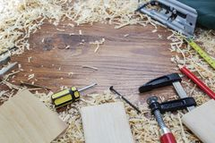 Electric jigsaw, screwdriver, screws, screws, on old scratched wooden Board, work tools concept. Royalty Free Stock Photos