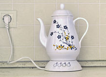 Electric kettle in the form of a decanter standing on a table Royalty Free Stock Photos
