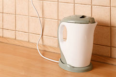 Electric kettle on wooden table in front of tiled wall angle view Royalty Free Stock Image