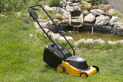 Electric lawn mower in the beautiful garden Royalty Free Stock Photos