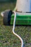 Electric lawn mower shallow depth of field artistic. Electric lawn mower on the garden Royalty Free Stock Photo