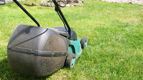 Electric lawnmower. Standing on green grass Royalty Free Stock Photos