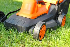 Electric lawnmower on green grass Royalty Free Stock Photos