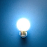 Electric light bulb. Glowing light bulb isolated on blue background Stock Image