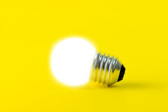 Electric light bulb. Glowing light bulb isolated on yellow background Stock Images