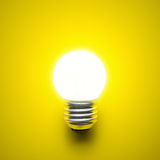 Electric light bulb. Glowing light bulb isolated on yellow background Royalty Free Stock Photography
