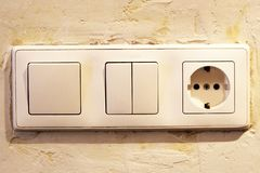 Electric light switch and socket on the empty wall, electrical power socket and plug switched. Object Stock Image