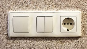 Electric light switch and socket on the empty wall, electrical power socket and plug switched. Object Stock Photography