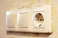 Electric light switch and socket on the empty wall, electrical power socket and plug switched. Object Stock Photos