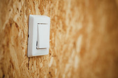 Electric light switch, wooden osb background Royalty Free Stock Image