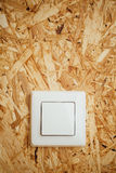 Electric light switch, wooden osb background Royalty Free Stock Photography